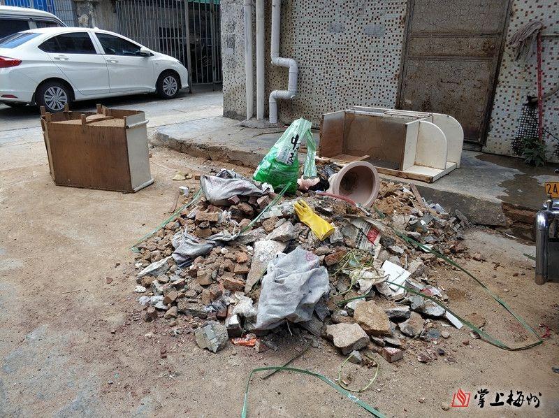小区楼前建筑垃圾成堆 梅城这栋居民楼的住户很烦恼